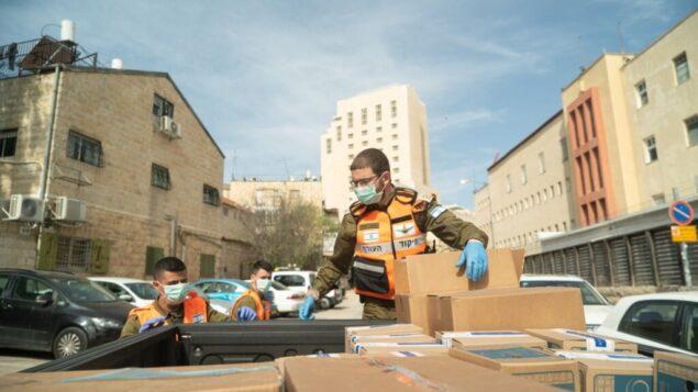 جندي يستعد لتوزيع رزم غذائية على سكان المدن والبلدات المصابة بفيروس كورونا، في صورة غير مؤرخة. (Israel Defense Forces)