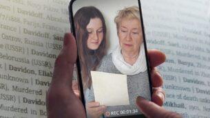 امرأة وفتاة تقرأن أسماء ضحايا المحرقة. (Courtesy of Yad Vashem)