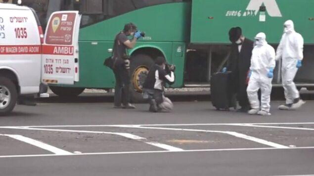 رجل إسرائيلي يشتبه في أنه استقل حافلة إلى القدس عمدا بعد تثبيت اثابته بفيروس كورونا، يرافق من قبل عاملي نجمة داود الحمراء الطبيين من الحافلة إلى سيارة إسعاف، 5 أبريل 2020. (Channel 12 screenshot)