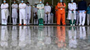 عاملون في مجال الرعاية الصحية يقفون دقيقة صمت لتكريم بزملائهم الذين توفيوا خارج مستشفى جريجوريو مارانون في مدريد، 14 مايو 2020 (GABRIEL BOUYS / AFP)