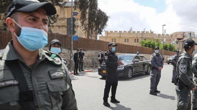 ضباط يقفون عند وصول قافلة تنقل رئيس الوزراء بنيامين نتنياهو إلى محكمة القدس المركزية، 24 مايو 2020 (Menahem KAHANA / AFP)