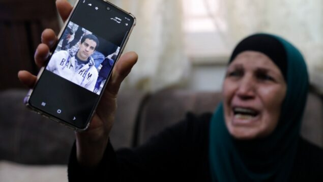 والدة رجل فلسطيني من ذوي الاحتياجات الخاصة، قالت الشرطة إنه قتل بالرصاص بعد اعتقادها خطأً أنه مسلح بمسدس، تبكي وهي تظهر صورتها على هاتفها الخليوي، في منزلها في القدس الشرقية، 30 مايو 2020. (Ahmad GHARABLI / AFP)