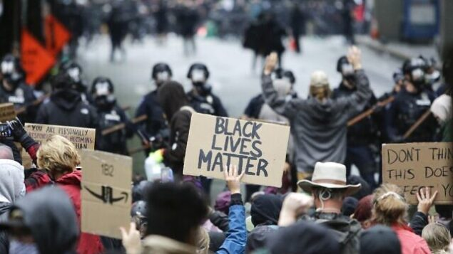 الشرطة تحاول تفريق المحتجين على وفاة جورج فلويد، رجل أسود توفي في 25 مايو في حجز شرطة مينيابوليس، في سياتل، واشنطن، 30 مايو 2020 (Jason Redmond / AFP)
