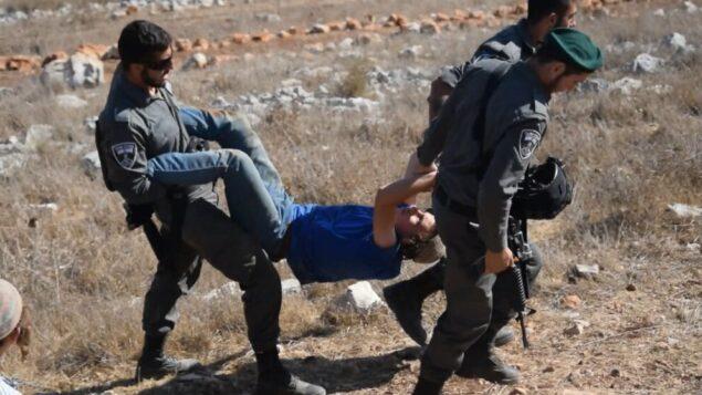صورة توضيحية: عناصر شرطة الحدود يحملون أحد عناصر 'شبان التلال' أثناء إخلاء بؤرة استيطانية غير قانونية في شمال الضفة الغربية. (Zman Emet, Kan 11)