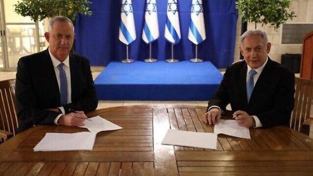 رئيس حزب 'أزرق أبيض'، بيني غانتس (يسار)، ورئيس الوزراء بنيامين نتنياهو يوقّعان على اتفاق حكومة الوحدة في 20 أبريل، 2020. (GPO)