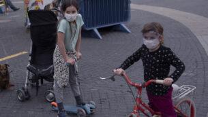 أطفال يرتدون أقنعة واقية في تل أبيب، 24 مارس 2020 (AP Photo / Oded Balilty)