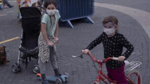 أطفال يضعون الكمامات في تل أبيب، 24 مارس، 2020.  (AP Photo/Oded Balilty)