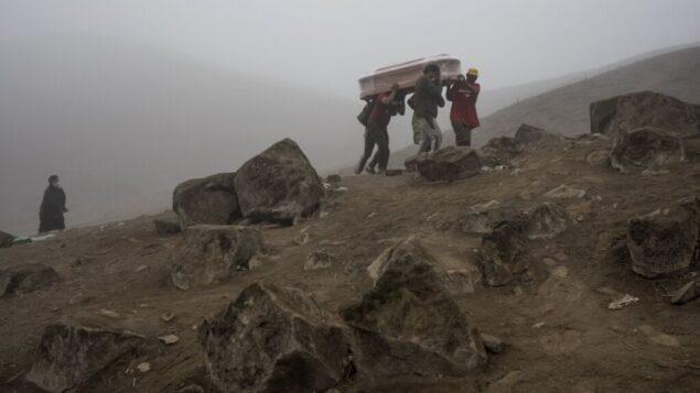 عمال المقبرة يحملون نعشا في مقبرة نويفا إسبيرانزا في ضواحي ليما، بيرو، 26 مايو 2020. (Rodrigo Abd / AP)