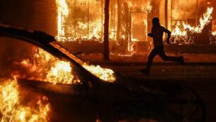 متظاهر يمر بين سيارات ومباني محترقة في شيكاغو أفنيو، في سانت بول، مينيسوتا، 30 مايو 2020 (AP Photo / John Minchillo)