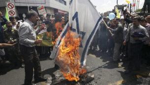 متظاهرون إيرانيون يحرقون العلم الإسرائيلي خلال تظاهرة سنوية لإحياء 'يوم القدس'، في طهران، 31 مايو، 2019. (AP Photo/Vahid Salemi)