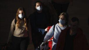 توضيحية: مسافرون يضعون الكمامات عند وصولهم إلى مطار بن غوريون،  27 فبراير، 2020.  (AP Photo/Ariel Schalit)