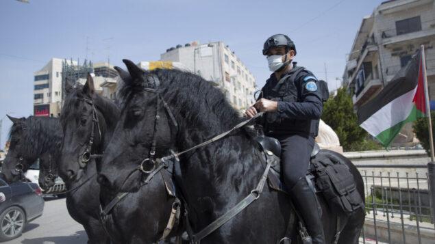 عناصر شرطة السلطة الفلسطينية على الخيول ينتشرون لفرض إجراءات ضد فيروس كورونا، في مدينة رام الله بالضفة الغربية، 23 مارس 2020. (AP Photo / Nasser Nasser)