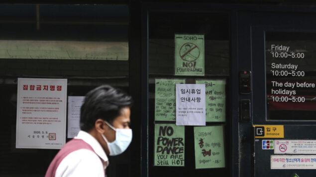 رجل يرتدي قناع وجه يمر امام مدخل نادي رقص مغلق مؤقتًا في سيول، كوريا الجنوبية، 10 مايو 2020 (AP Photo / Ahn Young-joon)