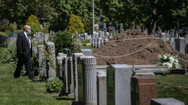 موظف يرتدي قناعًا وهو يفحص قبرا، بعد فترة وجيزة من دفن بدون وجود العائلة بسبب قيود فيروس كورونا، 13 مايو 2020، في مقبرة هولي كروس في بروكلين، نيويورك. (AP Photo / Bebeto Matthews)