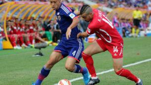 الياباني كيسوكي هوندا، يسار، والفلسطيني عبد الله جابر، يتنافسان على الكرة خلال مباراة كأس آسيا لكرة القدم بين اليابان وفلسطين في نيوكاسل، أستراليا، 12 يناير 2014. (Rob Griffith / AP)