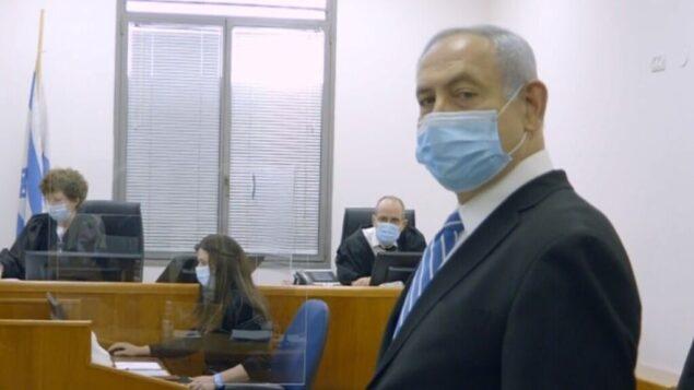 رئيس الوزراء بنيامين نتنياهو في بداية محاكمته بتهم الفساد، 24 مايو 2020. يظهر خلفه اثنان من القضاة الثلاثة في القضية، ريفكا فريدمان-فيلدمان وعوديد شاهام (Screen capture/Government Press office)