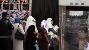فلسطينيون يتلقون رواتبهم في أحد البنوك في رام الله، الضفة الغربية، 17 مايو 2011. (Issam Rimawi/ FLASH90)