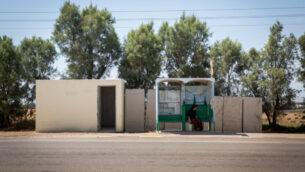صورة توضيحية: امرأة تنتظر في موقف للحافلات بالقرب من ملجأ عام، بالقرب من كيبوتز كفار عزة الجنوبي، 6 يوليو 2015. (Miriam Alster / FLASH90)