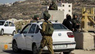 توضيحية: جنود إسرائيليون يقومون بتفتيش مركبات فلسطينية عند حاجز في قرية يطا بالضفة الغربية، 10 فبراير، 2017.(Wisam Hashlamoun/Flash90/File)