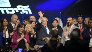رئيس الوزراء بنيامين نتنياهو (وسط) يلوح بينما يحيط به مشرعون من حزب الليكود في احتفال بعد الانتخابات في تل أبيب، 2 مارس 2020. (Gili Yaari / Flash90)