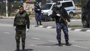 قوى الأمن الفلسطينية تقف عند مدخل مدينة نابلس في الضفة الغربية في 23 مارس، 2020، في إطار التدابير لإحتواء فيروس كورونا. (Nasser Ishtayeh/Flash90)