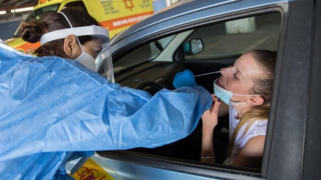إحدى أعضاء فريق طبي بزي واق تقوم بإجراء فحص لسيدة للكشف عن فيروس كورونا في مستشفى شعاري تسيدك بالقدس، 30 أبريل، 2020.(Nati Shohat/Flash90)