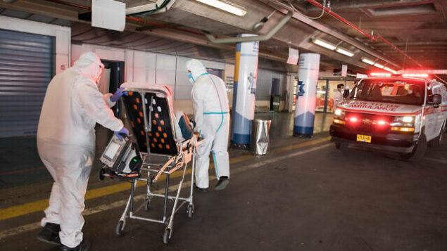 طواقم طبية بزي واق تنقل مريضا يُشتبه بأنه مصاب بفيروس كورونا إلى المركز الطبي شعاري تسيدك في القدس، 30 أبريل، 2020. (Nati Shohat/Flash90)