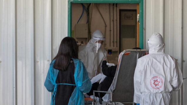 أفراد طاقم طبي في نجمة داوود الحمراء يرتدون زيا واقيا مع أحدى المرضى خارج وحدة فيروس كورونا في مستشفى شعاري تسيدك بالقدس، 30 أبريل، 2020. (Nati Shohat/Flash90)