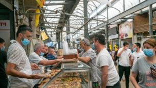 إسرائيليون يتسوقون في سوق في الرملة، 1 مايو 2020 (Yossi Aloni / Flash90)