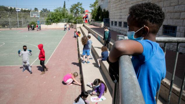 طلاب يرتدون أقنعة واقية للوجه عند عودتهم إلى المدرسة للمرة الأولى منذ تفشي فيروس كورونا، في القدس، 3 مايو 2020 (Olivier Fitoussi / Flash90)