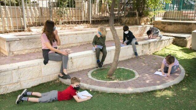 تلاميذ إسرائيليون يرتدون أقنعة واقية مع عودتهم إلى المدرسة للمرة الأولى منذ تفشي فيروس كورونا، 3 مايو، 2020 في القدس. (Olivier Fitoussi / Flash90)