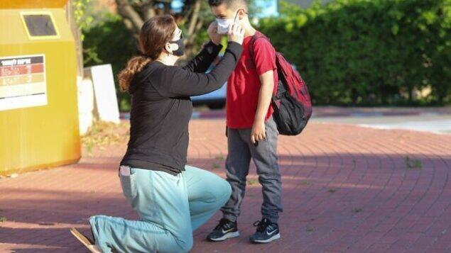 طفل إسرائيلي يضع قناع وجه قبل توجهه إلى المدارس في موشاف ياشرش، 3 مايو، 2020.(Yossi Aloni/Flash90)