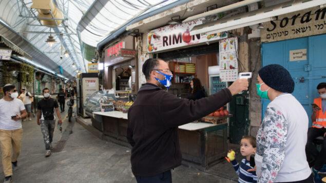 رجل يفحص درجة حرارة سيدة للتحقق مما إذا كانت تعاني من الحمى، عند مدخل سوق محانيه يهودا في القدس، 4 مايو 2020. (Nati Shohat / Flash90)