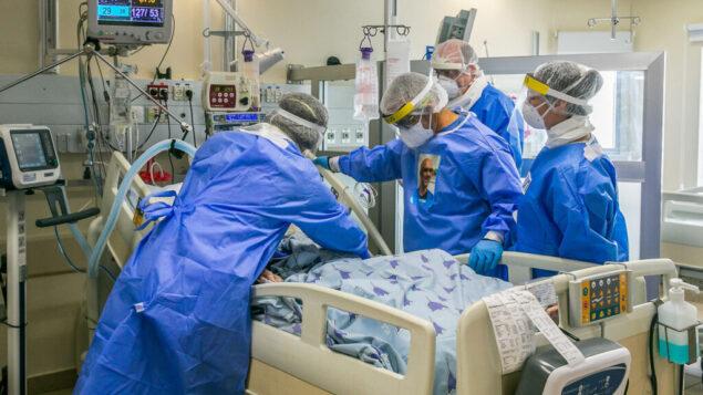 عاملون طبيون يعالجون مريضاً في جناح فيروس كورونا في مستشفى إيخيلوف في تل أبيب، 4 مايو 2020. (Yossi Aloni / Flash90)