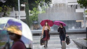 إسرائيليون يحملون مظلات في يوم ممطر في تل أبيب، 5 مايو، 2020.  (Miriam Alster/FLASH90)