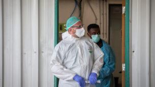 عاملان طبيان في زي واق يقفان من أمام وحدة فيروس كورونا في المركز الطبي شعاري تسيدك بالقدس، 5 مايو، 2020. (Nati Shohat/Flash90)