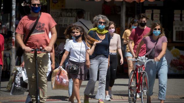 أشخاص يضعون أقنعة واقية في تل أبيب، 8 مايو، 2020. (Miriam Alster/Flash90)