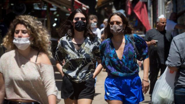 اشخاص يرتدون اقنعة وجه بينما يتسوقون في سوق الكرمل في تل أبيب، 8 مايو 2020. (Miriam Alster / Flash90)