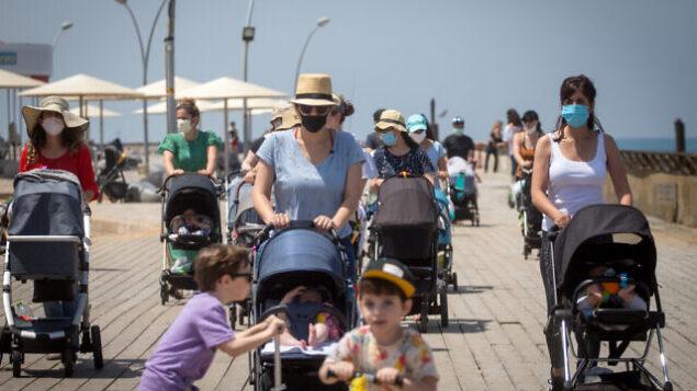 إسرائيليون يضعون أقنعة واقية في ميناء تل أبيب، بعد تخفيف القيود التي تم فرضها لاحتواء فيروس كورونا، 12 مايو، 2020.(Miriam Alster/FLASH90)