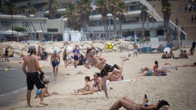 مستجمون إسرائيليون على أحد شواطئ تل أبيب في خرق للقواعد التي تهدف إلى وقف انتشار فيروس كورونا، 12 مايو، 2020.(Miriam Alster/FLASH90)