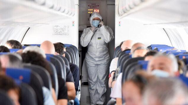 صورة توضيحية: عامل يرتدي زيا واقيا على طائرة في مطار بن غوريون، 13 مايو، 2020. (Yossi Zeliger/Flash90)
