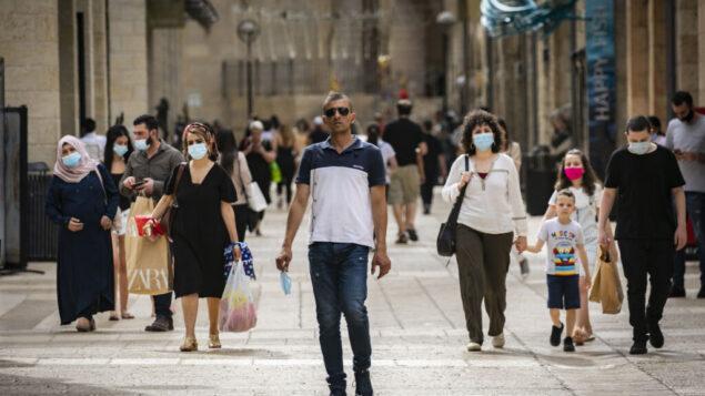 اشخاص يسيرون ويتسوقون في مركز ماميلا التجاري بالقرب من البلدة القديمة في القدس، 14 مايو 2020. (Olivier Fitoussi / Flash90)