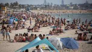 في تحد لقيود فيروس كورونا، يستمتع الإسرائيليون بالشاطئ في تل أبيب، بينما ارتفعت درجات الحرارة إلى 40 درجة مئوية في بعض أنحاء البلاد، 16 مايو 2020. (Miriam Alster / Flash90)