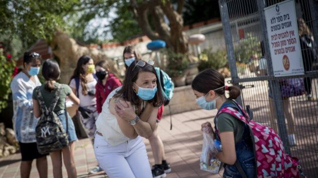 تلاميذ ومعلمون إسرائيليون يرتدون أقنعة واقية عند عودتهم إلى المدرسة، في مدرسة هشالوم في ميفاسيريت تسيون، بالقرب من القدس، 17 مايو 2020. (Yonatan Sindel / Flash90)