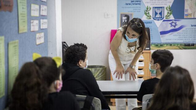 طلاب إسرائيليون ومدرسة يضعون الأقنعة الواقية مع عودتهم إلى المدرسة، في مدرسة 'هشالوم' في ميفسيرت تسيون، بالقرب من القدس، 17 مايو، 2020. (Yonatan Sindel/Flash90)