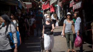 بعض الأشخاص يضعون الكمامات والبعض الآخر بدون كمامات في سوق الكرمل بتل أبيب، 26 مايو، 2020.  (Miriam Alster/FLASH90)