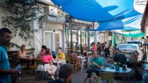 أشخاص يجلسون في مطعم في سوق الكرمل في تل أبيب، 26 مايو 2020 (Miriam Alster / FLASH90)