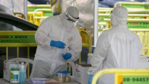 طاقم عاملين طبيين في نجمة داوود الحمراء يقومون بجمع عينات لفحوصات فيروس كورونا في القدس، 31 مايو، 2020. (Olivier Fitoussi/Flash90)