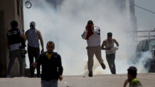 فلسطينيون يهربون من الغاز المسيل للدموع الذي أطلقه جنود إسرائيليون خلال اشتباكات في قرية يعبد في الضفة الغربية، 12 مايو 2020. (AP / Majdi Mohammed)