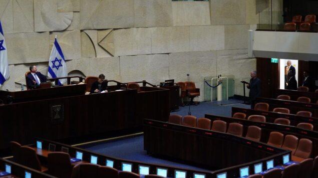 أعضاء الكنيست يصوتون واحدًا تلو الآخر في قاعة الكنيست لتشكيل أربع لجان، بما في ذلك لجنة فيروس كورونا، 24 مارس 2020. (Adina Veldman / Knesset)